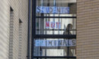 A student walks past a sign at Murano Street Student Village in Glasgow,