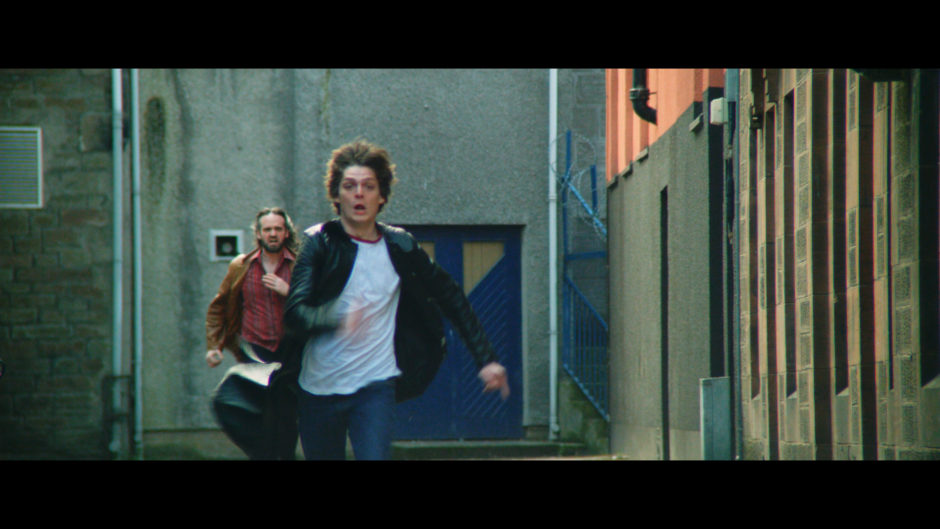 Actor Conor Berry, who plays rock promoter Dave McLean, in a chase scene from Schemers.