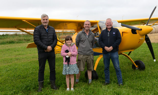 Pilot Martin Petrie and daughter Lucy (8) with farmer Andrew Stirling (left) and MAHSC chairman Stuart Archibald. Pic: Neil Werninck.
