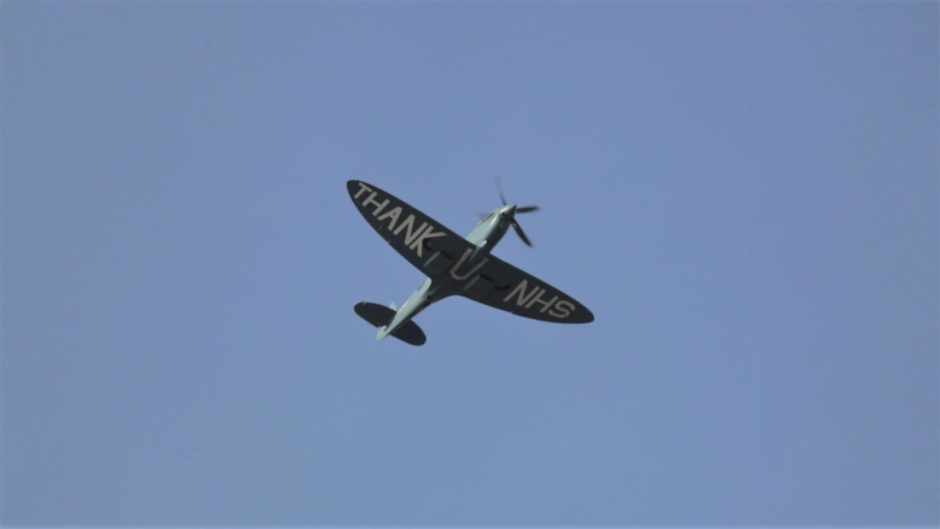 A Spitfire fighter plane passes over Dundee Law in a unique tribute to the NHS on Thursday.
