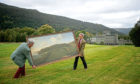 Staff members from Bonhams hold the painting Taymouth Castle and Estate including Loch Tay from the South, by the British artist John Sanger, on the hillside above Taymouth Castle in Kenmore.