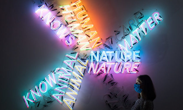 A Tate Modern employee views 'Human Nature / Knows Doesn't Know' during a photo call for the new Bruce Nauman exhibition at Tate Modern, London, the gallery's first new exhibition since reopening this summer. Nauman is recognised as one of the most innovative and influential artists of the late 20th and early 21st centuries.