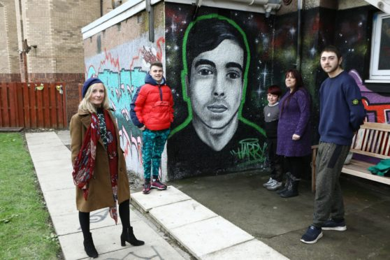 From left: Dawn Mullady, manager of the Pitstop Project, Caleb Fegan, friend of Harry, Ashley Carle, Harry's mum, Kalel Carle Harry's brother, and Nathan Hayes - friend of Harry, beside the new mural of Harry, by Sykes, at the Pitstop Project in Forfar.