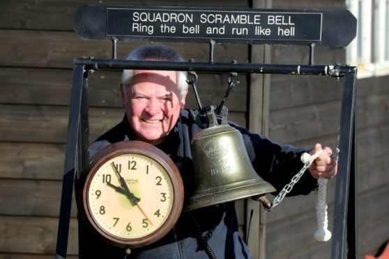 Montrose Air Station Heritage Centre chairman Stuart Archibald with the station clock and scrambling bell of the era.