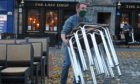 A man stacks away chairs outside The Last Drop pub as it closes in The Grassmarket, Edinburgh, after temporary restrictions announced by First Minister Nicola Sturgeon to help curb the spread of coronavirus.