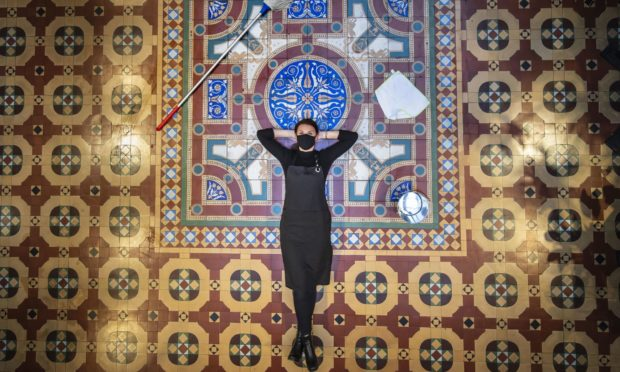 Bar Convent employee Lauren Masterman relaxes after cleaning a historic George and Arthur Maw tiled floor created in 1867, one of only two surviving examples of this assemblage of tiles, at England's oldest living convent Bar Convent. Visitors to the convent are being invited to follow in the footsteps of residents from the last 150 years and enjoy the historic space decorated with rare 19th century floor tiles. PA Photo. Picture date: Tuesday October 13, 2020. The floor was originally an outdoor yard and was made for the religious order of sisters living in the Grade 1 listed convent at the time. PA Photo. Picture date: Tuesday October 13, 2020.  Photo credit should read: Danny Lawson/PA Wire