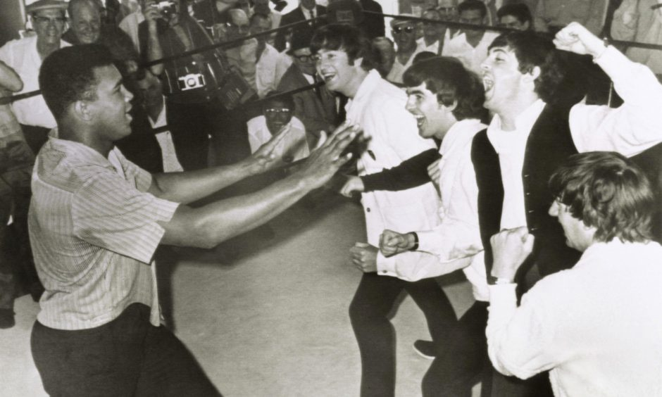 The Beatles John Lennon, George Harrison, Paul McCartney, and Ringo Starr pretend to gang up on boxer Cassius Clay (aka Muhammad Ali) on a visit during their first US tour in 1964