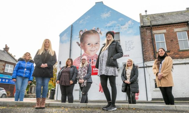 Arlene Falconer, Donna Forrester, Annilie Muller, Amy Jeffrey, Danielle Falconer, Aisha Ferguson, and Carlin Robertson next to the mural in Townhill.