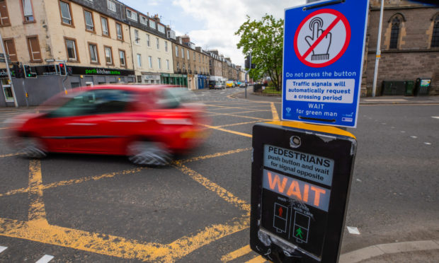 Do Not Touch signs were placed at pedestrian crossings across Perth and Kinross at the end of lockdown