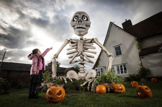 EMBARGOED TO 0001 TUESDAY OCTOBER 27  EDITORIAL USE ONLY  Francesca Bromham, aged six, looks up at a 13-foot-high animatronic skeleton which forms part of a Halloween display created using Samsung's SmartThings technology, Stevenage. PA Photo. Issue date: Tuesday October 27, 2020. The Old Bury is a 300 year-old property in Stevenage and has been transformed using projection mapping, animatronics, live action and a field of smart tech powered pumpkins. The show has been created following research which found that almost half of British adults would consider using smart home tech to elevate their Halloween celebrations at home this year. Photo credit should read: Matt Alexander/PA Wire
