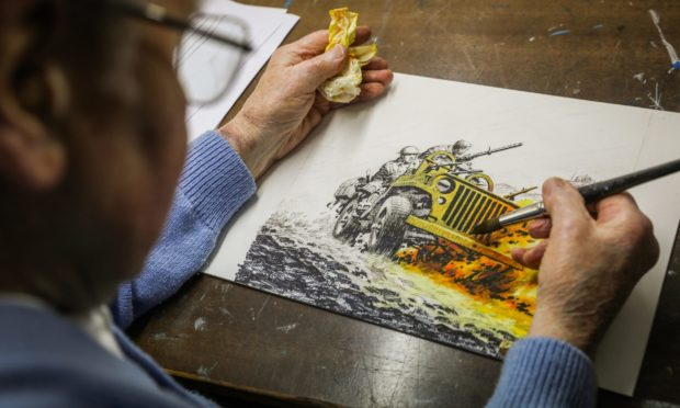 Illustrator Ian Kennedy in his studio working on a Commando image.