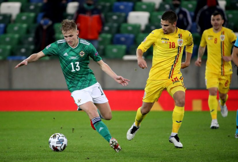 Ali McCann in action for Northern Ireland against Romania.
