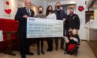 Legion Scotland National Chairman Charlie Brown (left) and his wife Margaret Brown, Forfar Legion branch chairman and secretary(right) receiving the cheque from Kylie Long, David McDowall and children Amelia (14), Darcy (10) and Thea(3).
