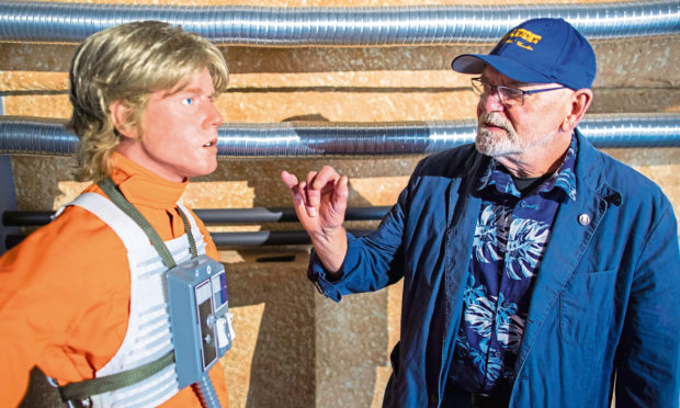 Actor Angus MacInnes, who played the role of Gold leader Jon 'Dutch' Vander in Star Wars, stands in front of the silicone replica of one of the main characters of the Star Wars films, Luke Skywalker.