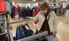 A woman shops in a near deserted Debenhams store