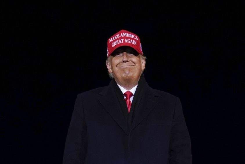 President Donald Trump smiles at supporters after a campaign rally at Gerald R. Ford International Airport, early Tuesday, Nov. 3, 2020, in Grand Rapids, Michigan.