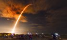 Crowds on the beach in Cape Canaveral, Fla., watch the launch of the SpaceX Falcon 9 Crew Dragon.