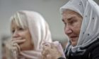 Bosnian women are overwhelmed by emotion watching the final moments of former Bosnian Serb military chief Gen. Ratko Mladic's trial at the memorial center in Potocari, near Srebrenica, Bosnia, in 2017