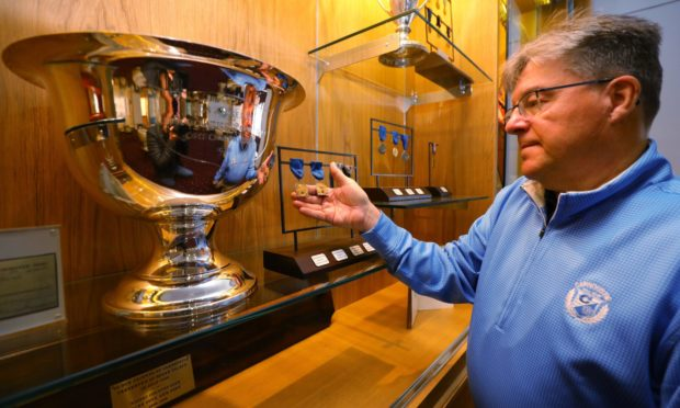 Bill Thompson of Carnoustie Golf Club with the Los Angeles Open trophy and medals from 1928, 29, 32 and '34, at Carnoustie Golf Club.