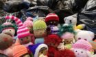 Knitted soft toys sit among the hundreds of bags of aid bound for Syria.