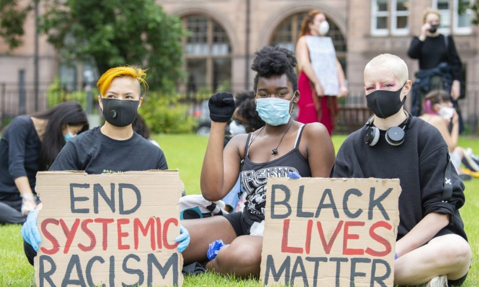 """Protesters gather near the Melville Monument in St Andrews Square, Edinburgh, for the """"Justice For Slaves"""" demonstration organised by Black Lives Matter Scotland."""
