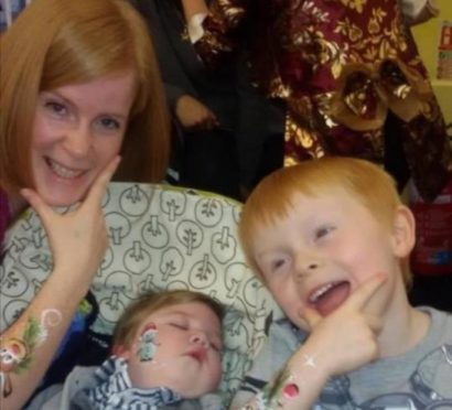 Jaxon Stars, centre, with mum Lisa and brother Anthony.