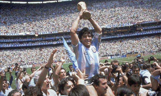 Diego Maradona holds up his team's trophy after Argentina's 3-2 victory over West Germany at the World Cup final at Atzeca Stadium in Mexico City.