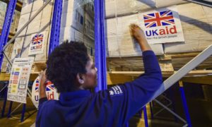 UK Aid stickers are placed on to cargo pallets containing British aid items destined for areas suffering humanitarian crisis at DFID's UK Disaster Response Operations Centre at Cotswold Airport, Kemble.