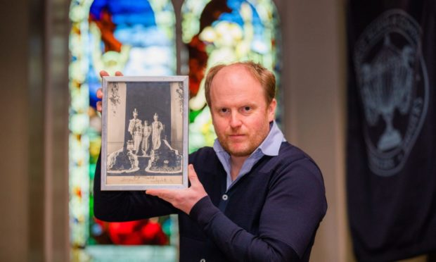 Auctioneer Nick Burns holding a signed portrait of the Royal Family in 1937 showing King George VI, Queen Elizabeth, Princesses Elizabeth and Margaret.