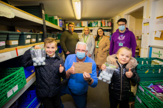 Kaeden Esslemont visiting the foodbank to donate the funds - front left is Kaeden alongside foodbank manager Norman Brown and sister Rhian - back row, left to right is dad Iain, mum Emma and sister Shannon, with foodbank volunteer Jamie Samson