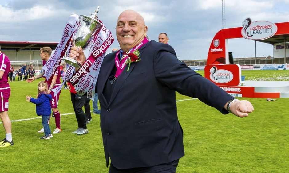 Dick Campbell celebrating on the field with the Scottish League 1 trophy