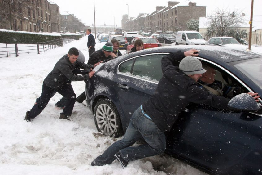 New snow storms wreak havoc across Dundee; This driver was lucky enough to get a team of willing helpers to get him on the move in Caird Avenue.