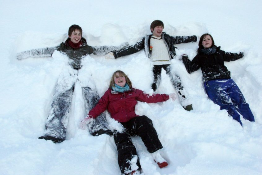 Snow in Scotland. Dundee University medical students (from left) Alex Dean (21), Fiona Stark (21), Russ Reynolds (20) and Laura Fotheringall (20) make snow angels on Dundee's Law.