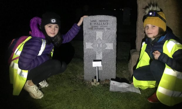 Two of the Cupar Scouts at one of the war graves in Cupar Cemetery where Remembrance respects were paid