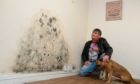 Clinton Lavery next to the mouldy wall
