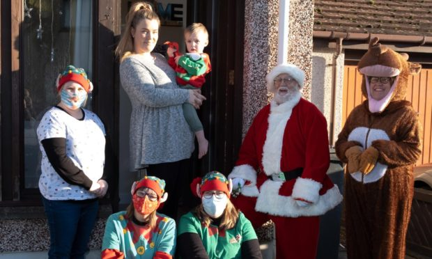 Kim Marr delivering Christmas goodies to mums in Arbroath.  Picture shows Mum Nadia Hawley with son Benny(2) and L to R: Pamela Ramsay, Louise Smith, Tracy Bedwell Santa Claus and Kim Marr. Picture: Paul Reid.