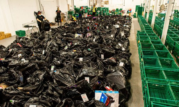 The green boxes are for families, and each black bag is filled with presents for a child.
