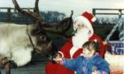 Three-year-old Kylie Barclay from Dundee with Santa Claus and his reindeer at the Deer Centre near Cupar in 1990.