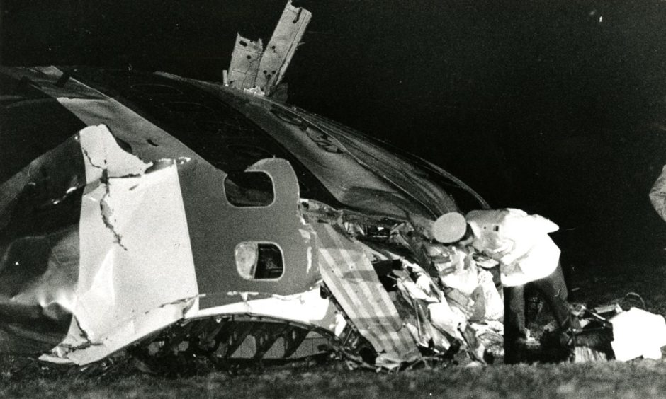 A policeman has a closer look at the nose of the stricken aircraft.