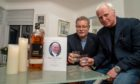 John Barr Jnr and Kris Nickolic with a bottle of 'John Barr' branded whisky. The pair plan to open the rare bottle and toast the memory of their dad/father-in-law -John Barr Snr - at his funeral this week.