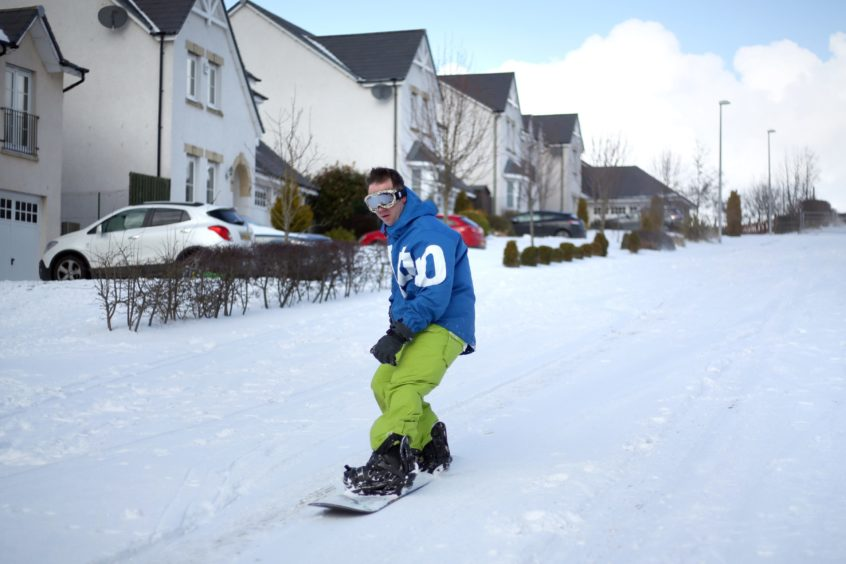 Snowboarder Kevin Trueland rides down Balmossie Road in the deep snow in Maerch 2018.