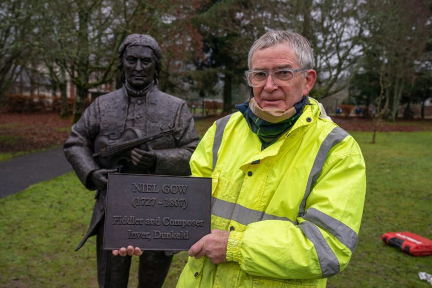 Sculptor David Annand with his piece after it was lowered into place.