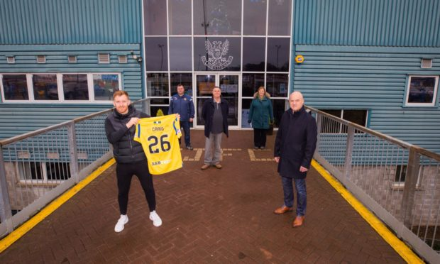 Liam Craig's shirt, auctioned off by Derrick Allan, front right, has raised £1,000 for Letham4all.