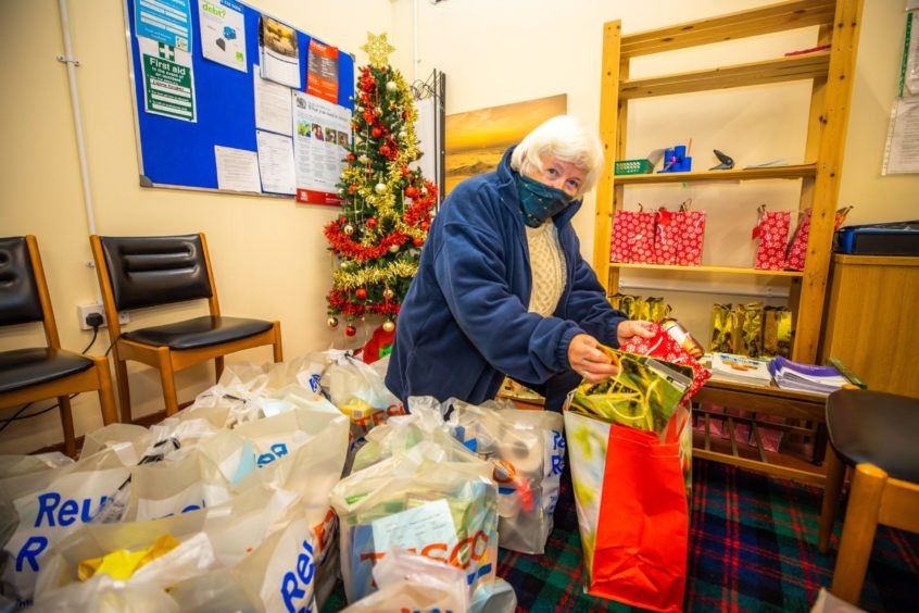 Marjorie organises food parcels in preparation for collection.