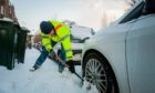 Mark Smith digs his car out of the snow to attempt to get to work on Windsor Terrace, Perth on March 1 2018.