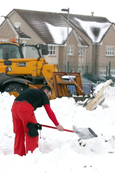 A man begins clearing the grounds of Kinnaird Primary School, as the cold weather continues on March 3 2018.
