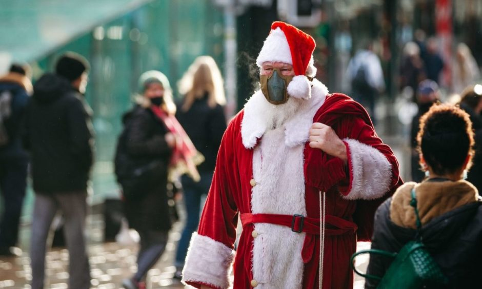 A man dressed as Santa as people do some last minute Christmas shopping in Glasgow.