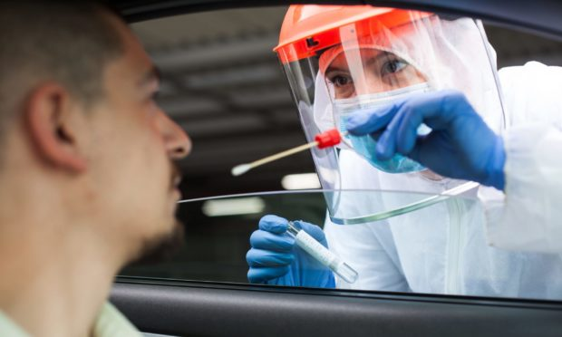 A NHS worker performing a drive-thru COVID-19 test.