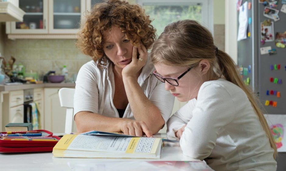 Mother helping daughter with her homework at the table in the dining room. Home Schooling concept.; Shutterstock ID 425607454
