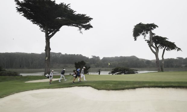 Collin Morikawa walks to the 17th green in the final round of the PGA Championship with no fans in attendance.